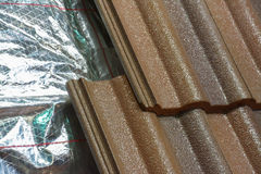 Installing roof insulation. In a home to reduce heat wastage and heating bills, and help reduce global warming Stock Image