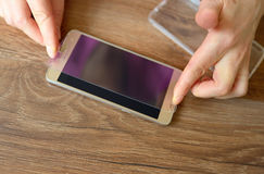 Installing safety glass on smartphone Royalty Free Stock Image
