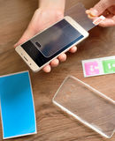 Installing safety glass on smartphone Stock Photography