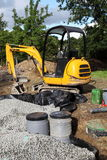 Installing A Sand Filter With A Mini Digger. Using a mini digger to install a sand and gravel filter bed with pipes, filters and plastic membrane, which is then royalty free stock images