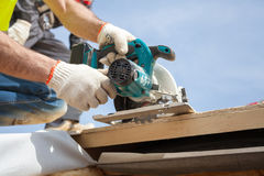 Installing a skylight. Construction Builder Worker use Circular Saw to Cut a Roof Opening for window. Installing a skylight. Construction Builder Worker use stock photos