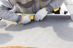 Installing Skylights in new home. Construction mason worker attach insulation material on Oriented Strand Board. Installing Skylights in new home. Construction stock photo