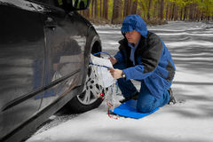 Installing Snow Tire Chains. The senior man is stopped along the roadside to install snow tire chains on his vehicle before proceeding farther down the road Stock Image