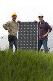 Installing Solar Panels. Technicians installing solar panels, looking at camera Royalty Free Stock Photography