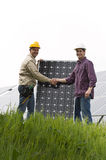 Installing Solar Panels. Technicians installing solar panels, shaking hands Stock Photography