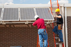 Installing Solar Panels. Two electricians installing solar panels on a building stock photos