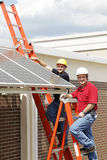 Installing Solar Panels DT. Electricians installing energy efficient solar panels on a school building royalty free stock image