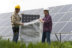 Installing Solar Panles. A couple of technicians installing solar panels Royalty Free Stock Images