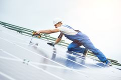Installing of solar photo voltaic panel system. Construction worker connects photo voltaic panel to solar system using screwdriver. Professional installing and Stock Image