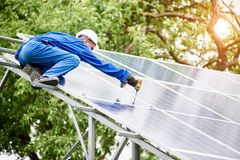 Installing of solar photo voltaic panel system. Team of two constructors connecting photo voltaic panel to stand-alone solar system platform using screwdriver Stock Images