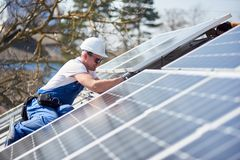 Installing solar photovoltaic panel system on roof of house royalty free stock photo