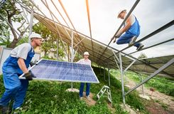 Installing of solar photo voltaic panel system. Installing of stand-alone solar photo voltaic panel system. Three technicians lifting big solar module on high Royalty Free Stock Photo