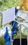 Installing of solar photo voltaic panel system. Installing of stand-alone solar photo voltaic panel system. Workers in hard-hats and blue overall lifting the Stock Images