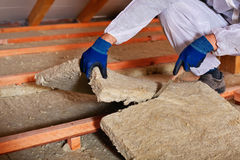 Installing thermal insulation layer - closeup on hands Stock Photography