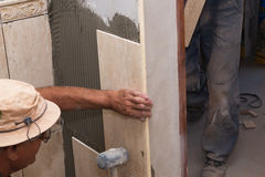 Installing tiles. Tiles installation on the corner of wall Royalty Free Stock Photography
