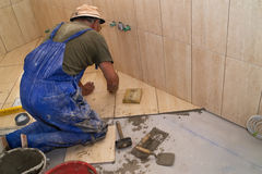 Installing tiles. On the floor, a nice rustic design royalty free stock image