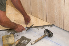 Installing tiles. Installing tile on the floor and grab for the underlaying layer royalty free stock photo