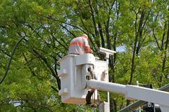 Installing Traffic Camera. A man in a lift bucket installing a traffic camera on a traffic light Royalty Free Stock Photo