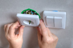 Installing the wall outlet into a wiring box, close-up hands. Royalty Free Stock Image