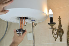 Installing a water heater. Man`s hand installing a new water heater in a boiler stock photography