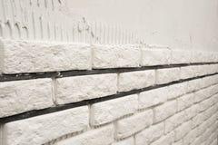 Installing white decorative bricks Stock Images