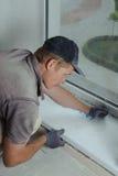 Installing window sill. Worker installs plastic sill using polyurethane foam Royalty Free Stock Photo