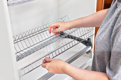 Installing wire dish rack for drying dishes inside kitchen cabin Stock Photo