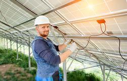 Installing of solar photo voltaic panel system. Installing and wiring of stand-alone solar photo voltaic panel system. Close-up of young electrician in hard-hat Royalty Free Stock Photography