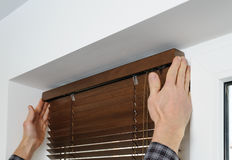 Installing wooden blinds. A man attaches a decorative bar on top Stock Images