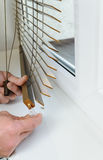 Installing wooden blinds. Man attaches the plastic braket to the bottom plank Royalty Free Stock Photos