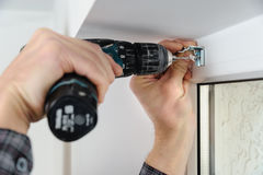 Installing wooden blinds. A man drill hole for fastening metal bracket that holds the jalousie Royalty Free Stock Photo