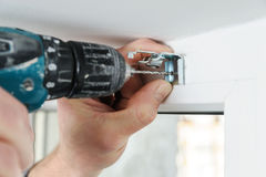 Installing wooden blinds. A man drill hole for fastening metal bracket that holds the jalousie Stock Photo