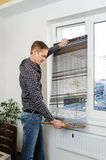 Installing wooden blinds. A man holds the unfolded jalousie Royalty Free Stock Photos