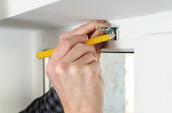 Installing wooden blinds. Man marks the place of mounting jalousie on the windows Royalty Free Stock Image
