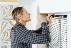 Installing wooden blinds. Man marks the place of mounting jalousie on the windows Royalty Free Stock Photo