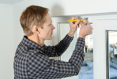 Installing wooden blinds. Man marks the place of mounting jalousie on the windows Stock Image