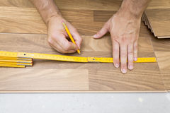 Installing wooden laminate flooring Royalty Free Stock Image