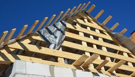 Installing wooden rafters, logs, eaves, timber on new house roofing construction. Close up royalty free stock photography
