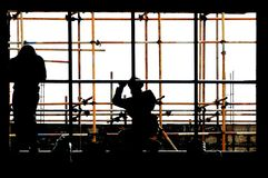 Installs the window. A factory architectural engineering, the worker is installing the window Royalty Free Stock Photo