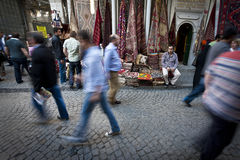 Instanbul Rug Merchant. ISTANBUL, TURKEY – APRIL 26: Carpet merchant outside the Grand Bazaar in Istanbul on alleyway with tourists and local Turkish people Stock Image