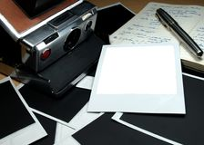 Instant camera. Vintage instant camera and whitel photo frame royalty free stock photography