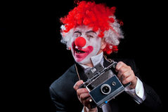 Instant camera clown winking. Colorful clown with an instant camera on a black background Royalty Free Stock Photo