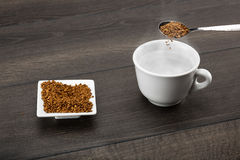 Instant coffee. Granules poured from a table teaspoon into hot steamy water. Shallow depth of field royalty free stock photos