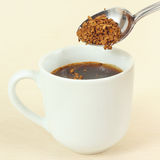 Instant coffee is poured from spoon in a cup Royalty Free Stock Photography
