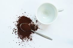Instant coffee powder on silver soon and cup in white background royalty free stock images