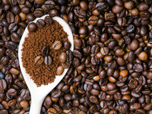 Instant coffee in spoon on coffee beans Royalty Free Stock Image