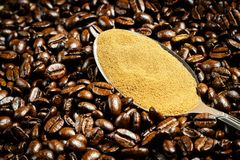 Instant coffee in spoon on coffee beans background Royalty Free Stock Photos