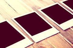 Instant empty polaroid photos frames on wooden background. Stock Photos