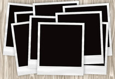 Instant Film Photos In a Pile. A pile of instant film photos arranged in a pile on a wooden table Stock Image