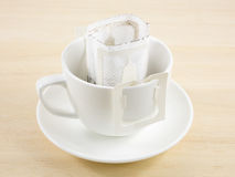 The instant freshly brewed coffee drip bag. On white coffee cup stock photos